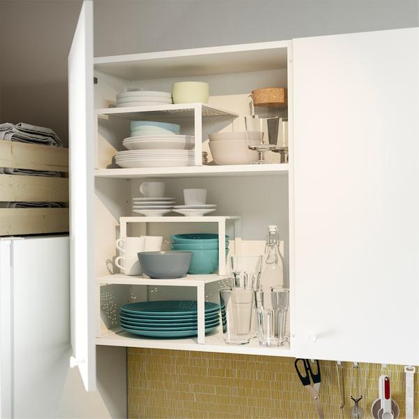 Une porte d'armoire de cuisine est ouverte et montre des demi-étagères blanches VARIERA qui organisent les assiettes, bols et autres.