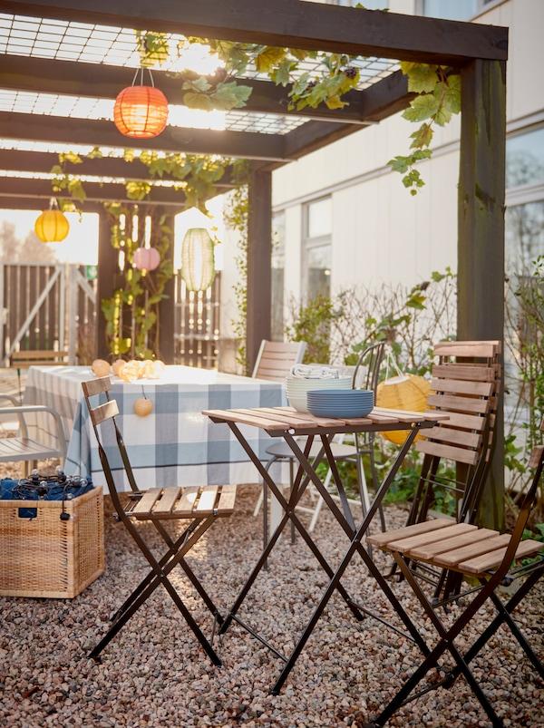 Une rangée de chaises et de petites tables en cours de préparation pour une fête sous une pergola décorée dans une cour.