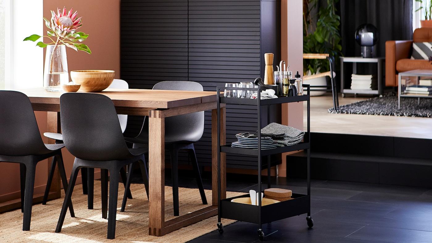 Une salle à manger avec des chaises anthracite, une table en plaqué chêne teinté, un rangement noir, un tapis en jute et une desserte avec de la vaisselle dessus.