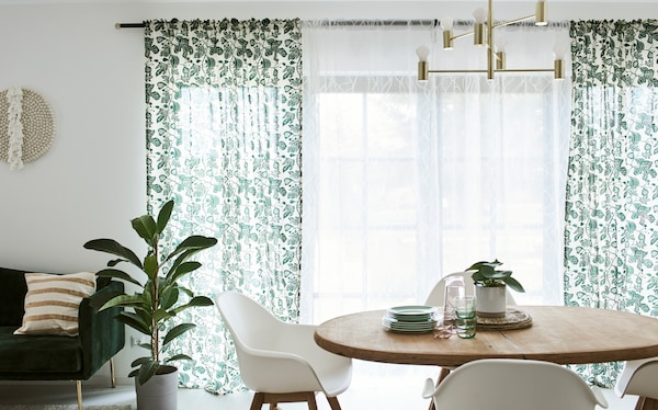 Une salle à manger avec une table en bois et des chaises blanches, devant une porte-fenêtre habillée de rideaux blancs et à motif de feuilles.
