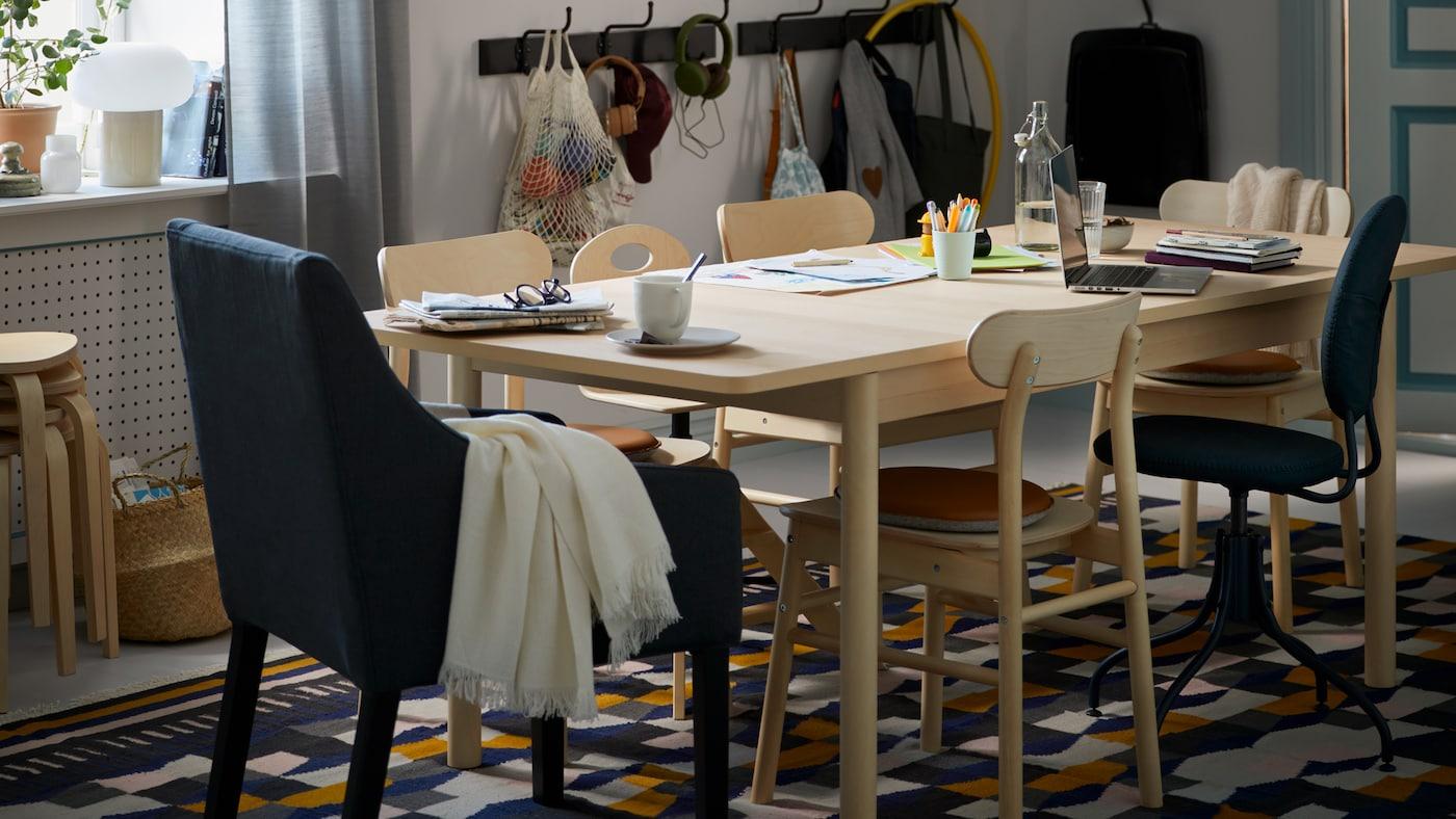 Une salle à manger avec une table en bouleau RÖNNINGE accueillant divers objets et des chaises RÖNNINGE sur un tapis TÅRBÄK.