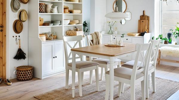 Une salle à manger avec une table en chêne/blanc, quatre chaises blanches, un tapis en jute et deux armoires hautes blanches avec deux portes chacune.