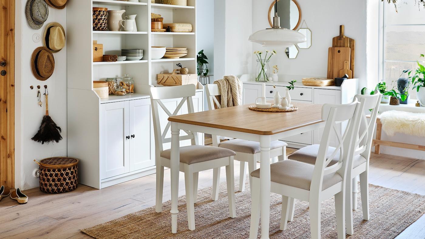 Une salle à manger avec une table en chêne blanche, quatre chaises blanches, un tapis en jute et des éléments hauts avec deux portes chacun.
