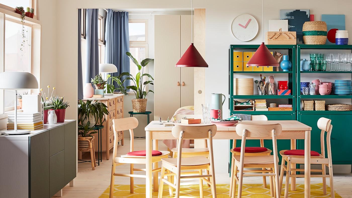 Une salle à manger avec une table et des chaises en bouleau, un tapis jaune, un agencement de rangement blanc et gris-vert et des suspensions rouge foncé.