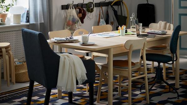 Une salle à manger avec une table RÖNNINGE en bouleau accueillant différents objets, et des chaises RÖNNINGE sur un tapis TÅRBÄK.