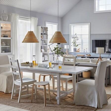 Une salle à manger spacieuse et lumineuse à côté d'une salle de séjour. La table à manger est déployée et les tabourets servent de sièges d'appoint.