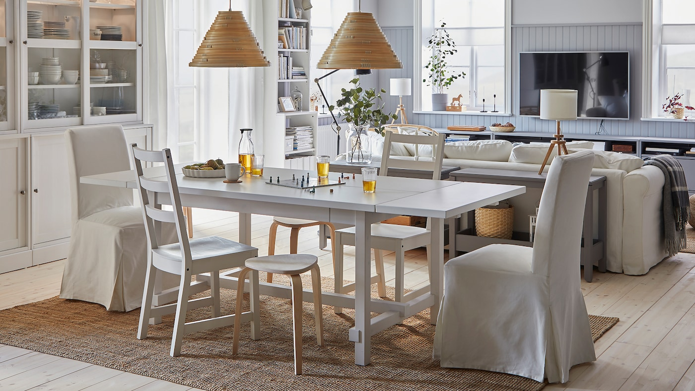 Une salle à manger spacieuse et lumineuse ouverte sur le salon. La table est dépliée, des tabourets offrent des assises supplémentaires.