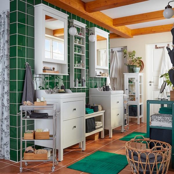 Une salle de bain avec du carrelage vert, deux lavabos, deux meubles à miroir, un panier en rotin et deux tapis de bain verts.