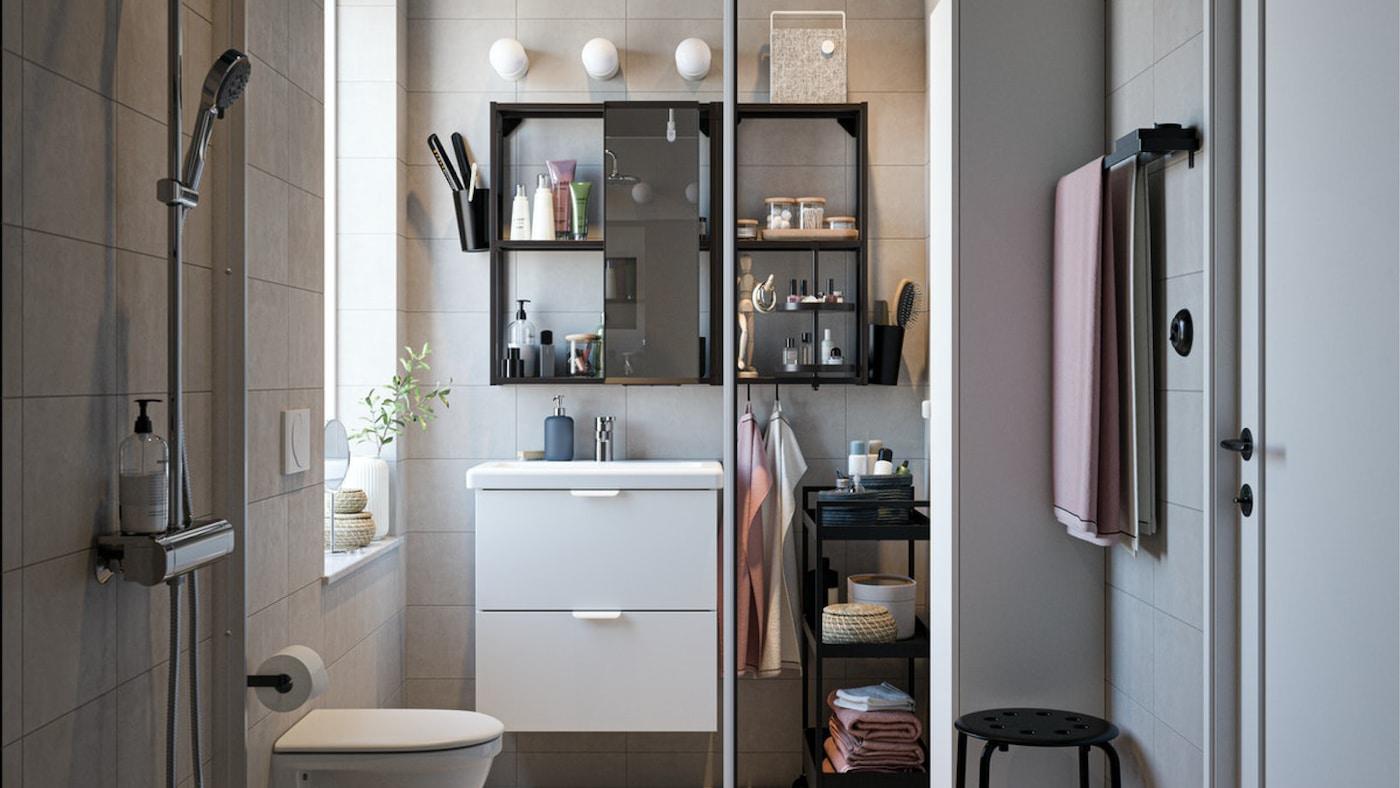 Une salle de bain avec du mobilier noir/blanc, un ensemble de douche chromé, des serviettes rose pâle et une porte de douche vitrée.
