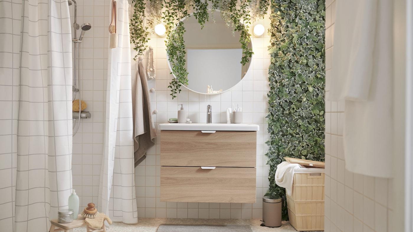 Une salle de bain avec une douche, des plantes artificielles FEJKA, un meuble lavabo ENHET/TVÄLLEN, un marchepied VILTO en bouleau et un miroir rond.