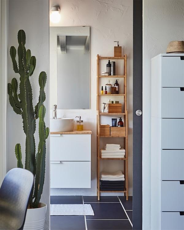 Une salle de bain avec une étagère en bambou RÅGRUND placée à côté d'un meuble lavabo blanc et d'un miroir accroché au mur.