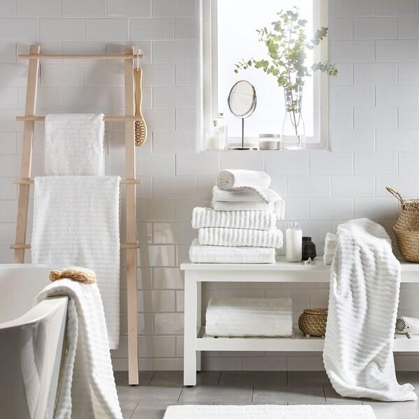Une salle de bain blanche, des carreaux blancs, une baignoire autoportante blanche, une échelle et un canapé blanc avec des serviettes blanches.