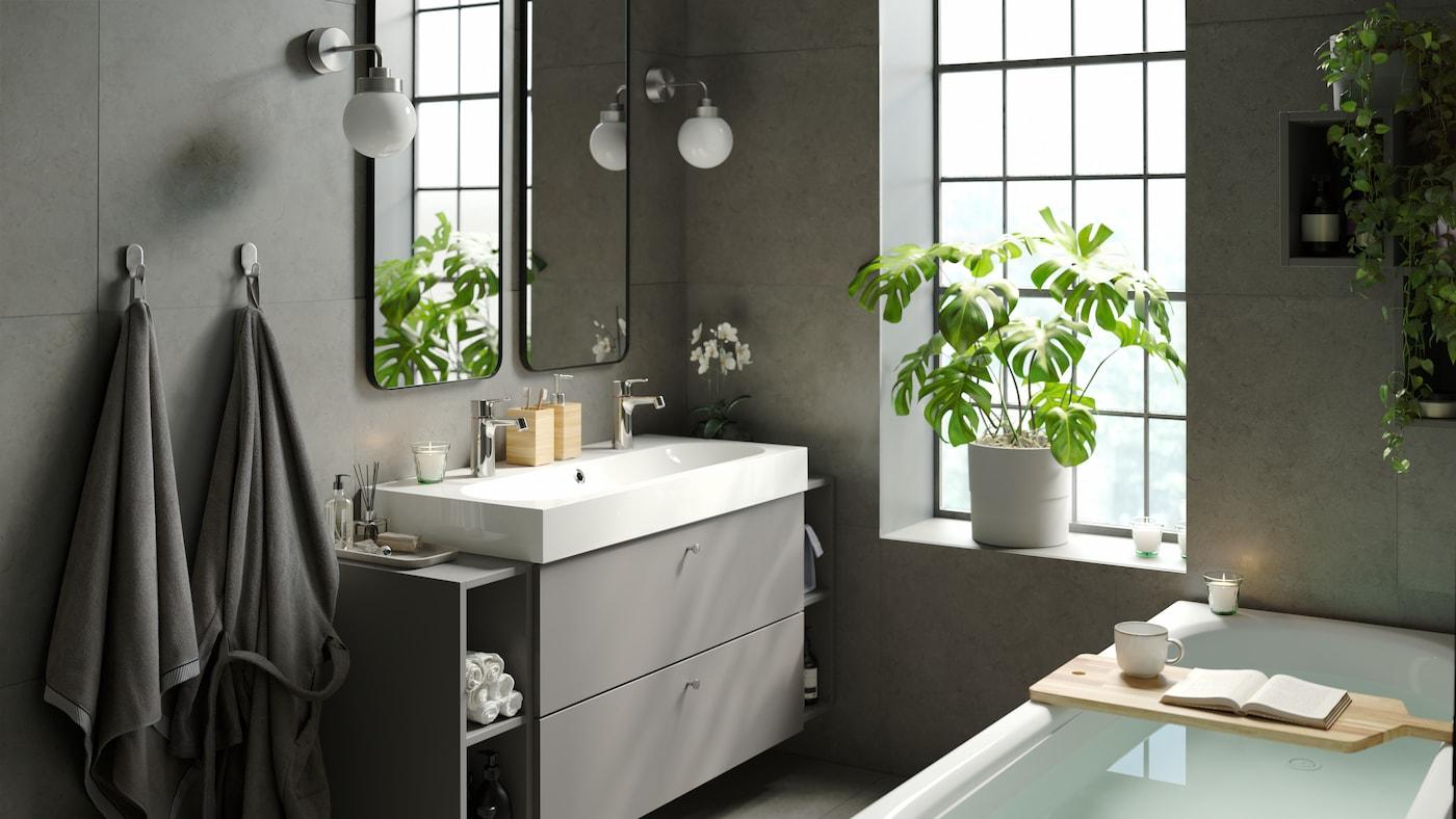 Une salle de bain calme et relaxante avec une baignoire moderne et élégante, un grand lavabo simple avec du rangement, deux miroirs et des plantes vertes d'intérieur.