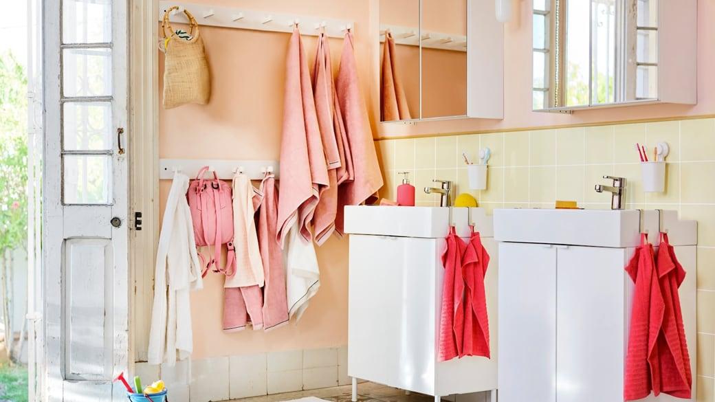 Une salle de bain lumineuse avec des serviettes rose et corail, et des sacs au mur.
