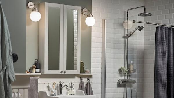 Une salle de bains à carreaux blancs et des murs vert clair, deux appliques FRIHULT de chaque côté d'une armoire à pharmacie GODMORGON.