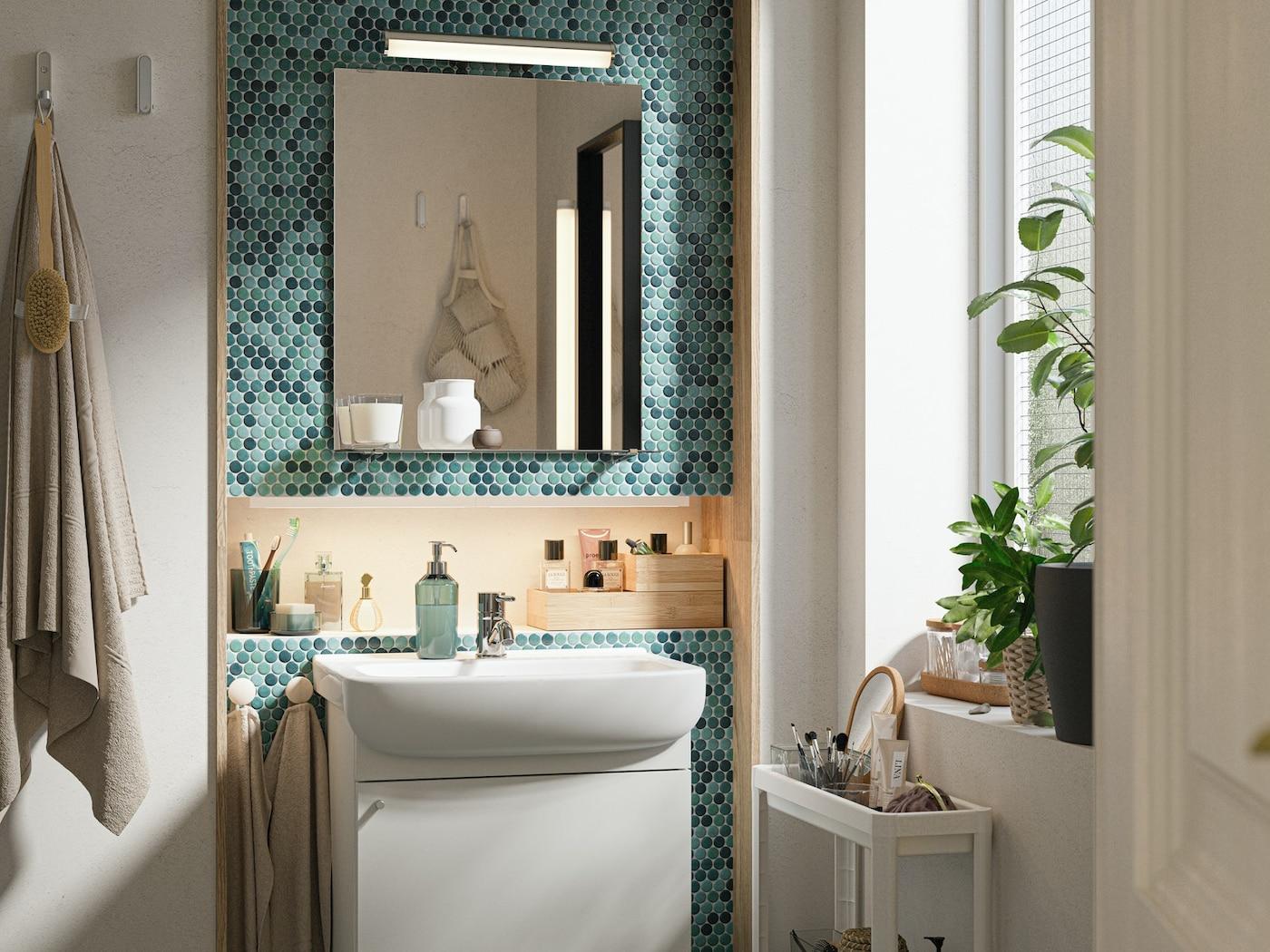 Une salle de bains aux carreaux verts, un ensemble de meubles de salle de bains blancs, un miroir avec une étagère, des plantes en pot sur un rebord de fenêtre.