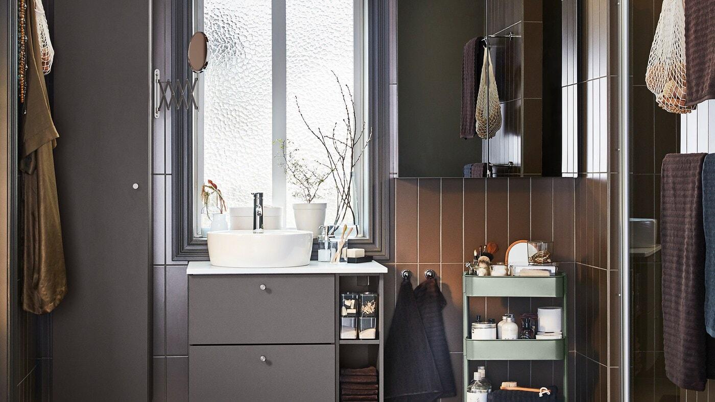 Une salle de bains aux meubles gris foncé, une armoire à porte miroir et une desserte gris-vert.