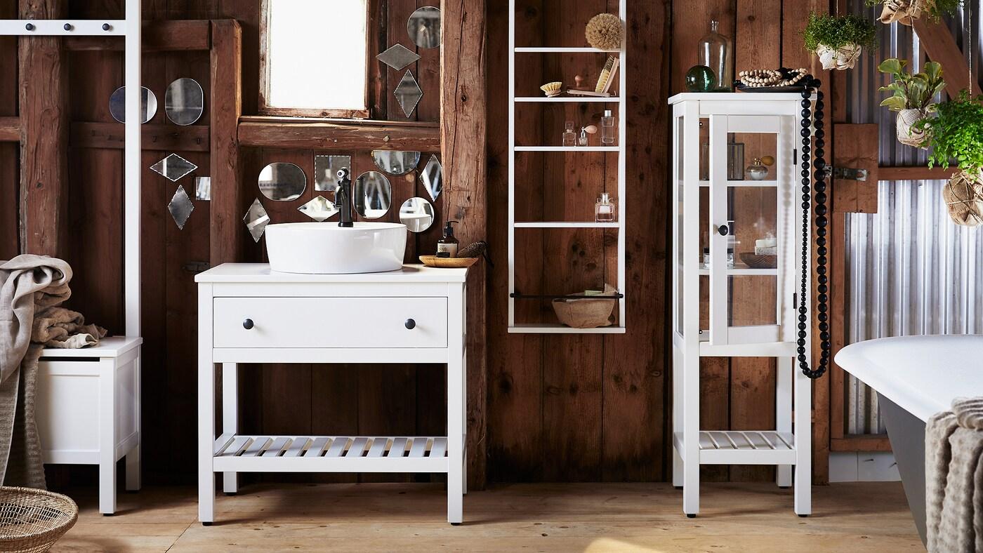 Une salle de bains avec des murs en bois foncé, couverts de petits miroirs aux formes irrégulières et avec des meubles de salle de bains HEMNES blancs.