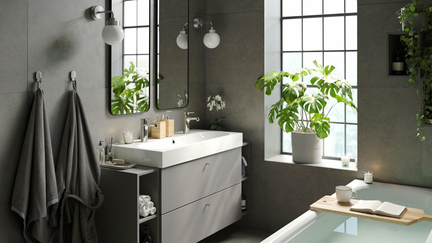 Une salle de bains calme et reposante avec une baignoire élégante, un évier à deux bacs avec du rangement, des miroirs doubles et des plantes vertes d'intérieur.