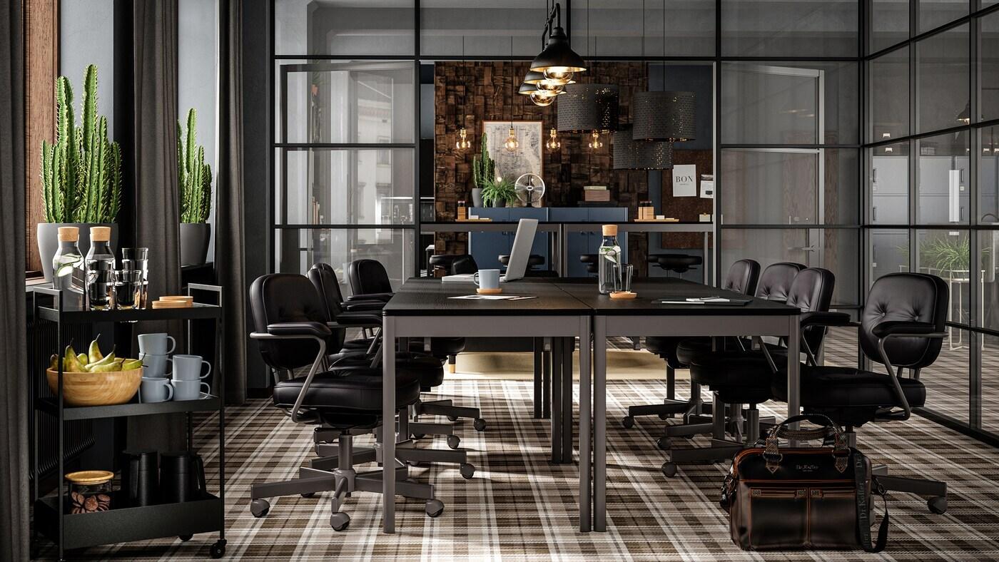 Une salle de conférence avec des meubles foncés, des murs vitrés, un plancher à carreaux brun, des sièges en cuir et des cactus près de la fenêtre.