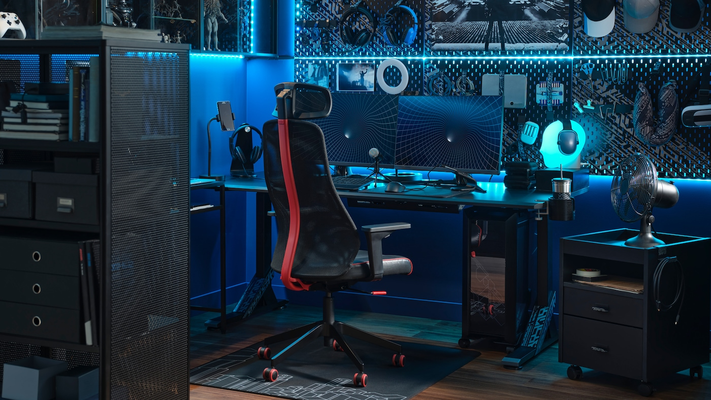 Une salle de gaming haute technologie avec un éclairage LED bleu et deuxécrans sur un bureau avec une chaise de gaming MATCHSPEL noire devant.