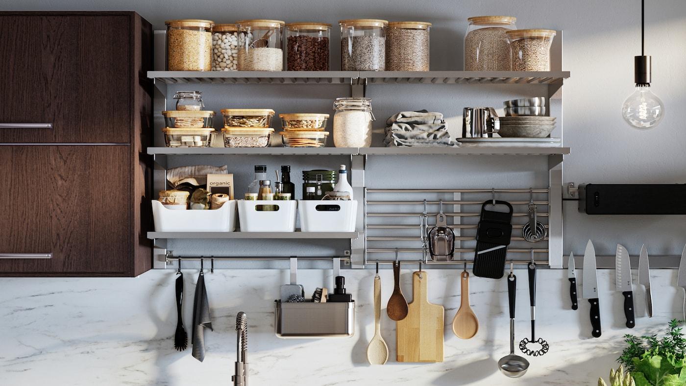 Une série de rangements de cuisine muraux KUNGSFORS avec des bocaux en verre avec couvercles, des boîtes de rangement VARIERA blanches et des ustensiles suspendus.