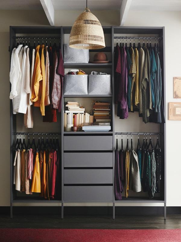 Une solution de rangement de vêtements symétrique composée d'une armoire-penderie AURDAL grise avec des tringles et des tiroirs.