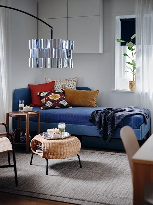 Une structure de lit matelassée avec une tête de lit en angle, un couvre-lit bleu, des coussins colorés et un repose-pieds avec rangement sur lequel se trouvent des collations.