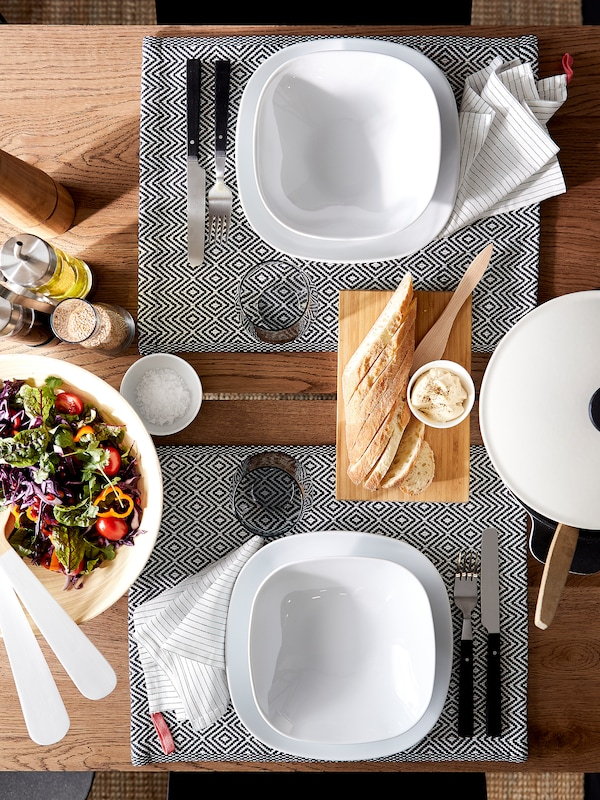 Une table à manger avec des assiettes et des bols blancs, des napperons à motifs, des couverts, des verres et un bol à salade.