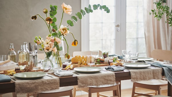 Une table à manger d'apparence rustique avec de grandes fleurs, des linges de maison et de la vaisselle blanche.
