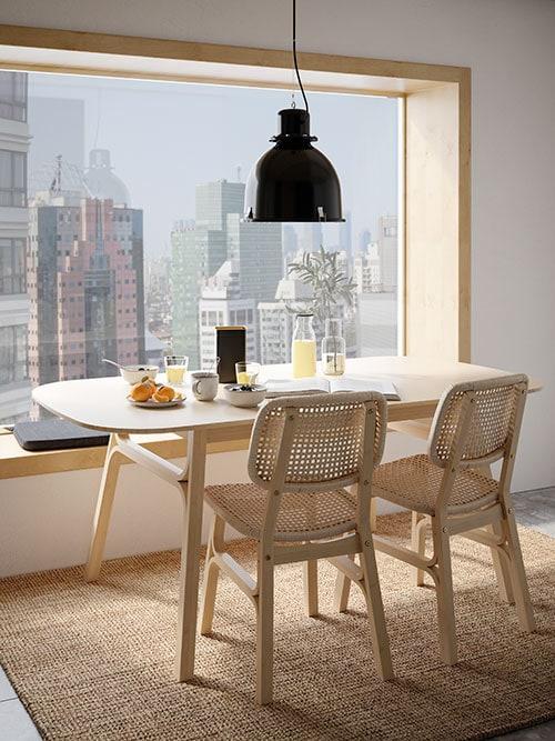 Une table à manger en bambou clair près d'une grande fenêtre donnant sur la ville, deux chaises en bambou clair et un déjeuner posé sur la table.
