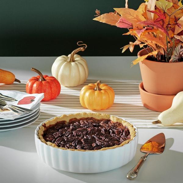 Une table avec le moule à tarteHÖSTPROMENAD rempli d'une tarte; des citrouilles et des feuilles d'automne se trouvent en arrière-plan.