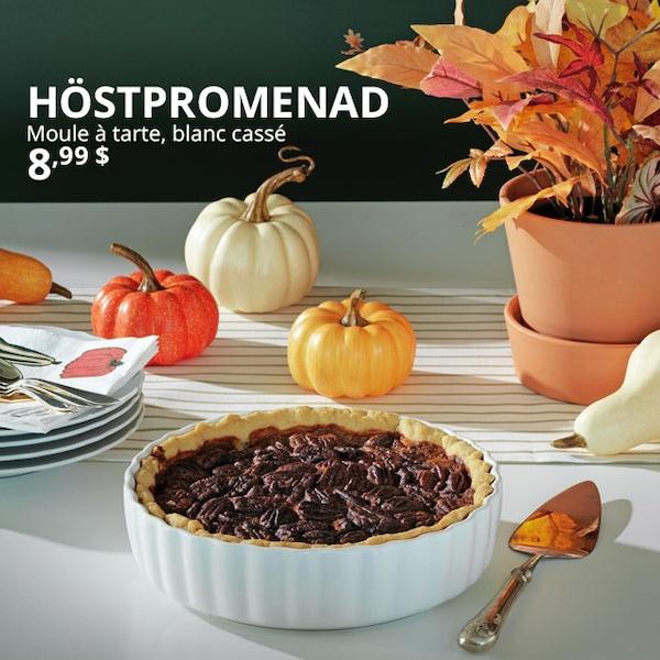 Une table avec le moule à tarte HÖSTPROMENAD rempli d'une tarte ; des citrouilles et des feuilles d'automne se trouvent en arrière-plan.