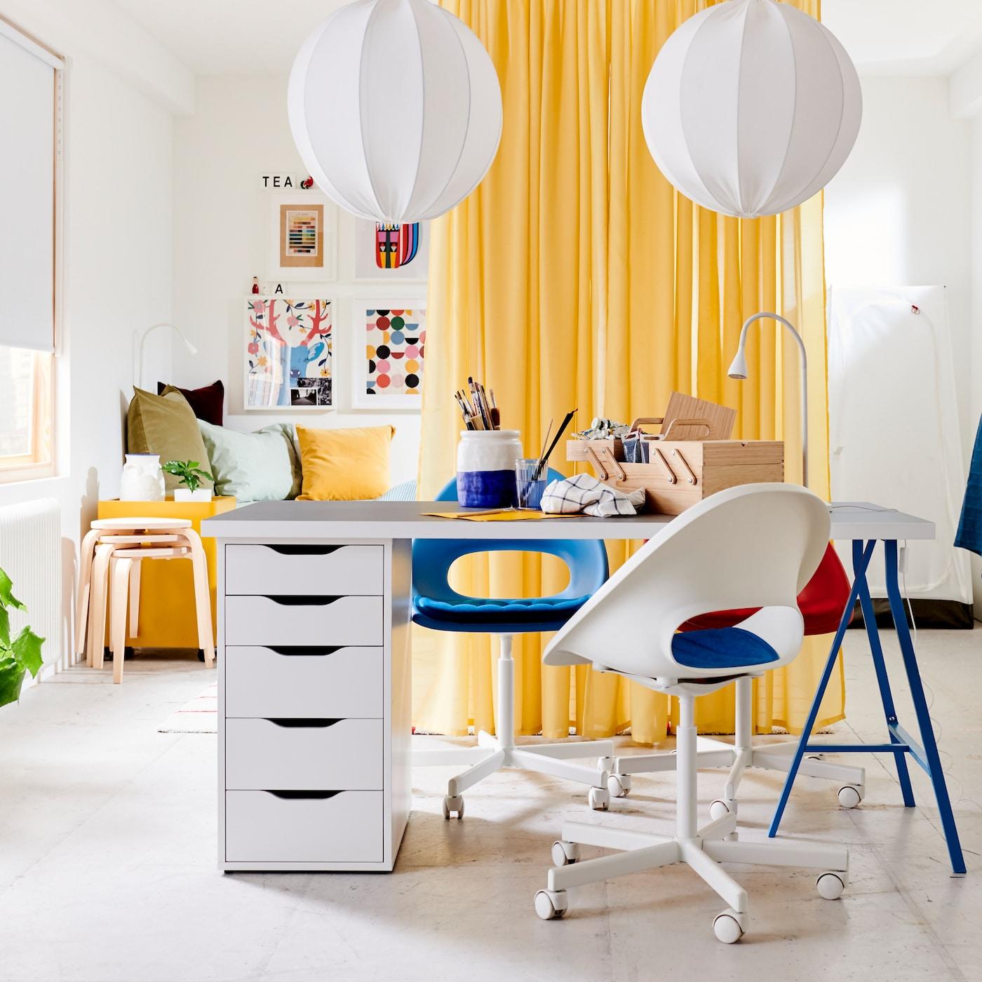 Une table blanche avec le dessus gris clair, des pieds bleus et un caisson à tiroirs, trois chaises pivotantes, une blanche, une bleue et une rouge, et des rideaux jaunes utilisés comme cloison de séparation.