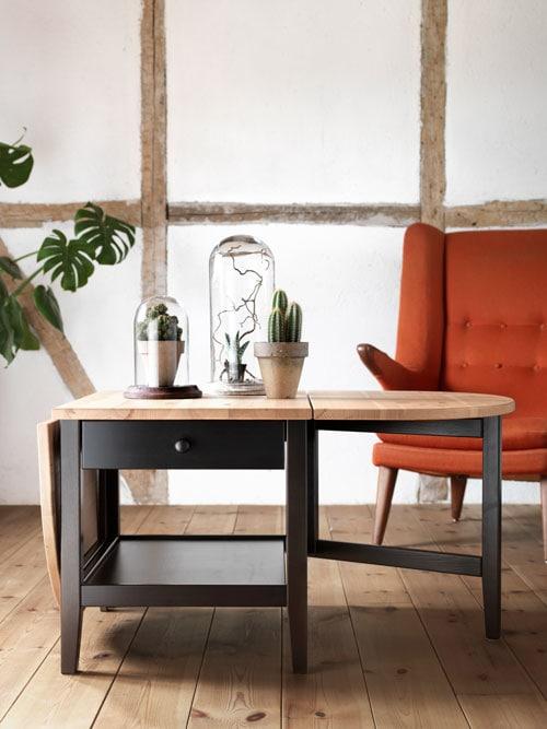 Une table brun foncé avec un plateau en bois clair, accompagnée d'un fauteuil orange en arrière-plan.