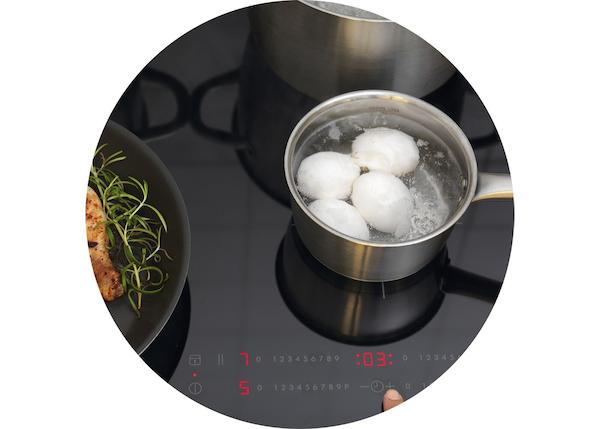 Une table de cuisson à induction IKEA surmontée d'une casserole IKEA dans laquelle on faire bouillir des œufs.