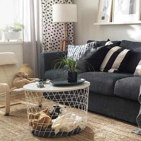 Une table de rangement blanche remplie de peluches dans un salon avec un canapé gris.