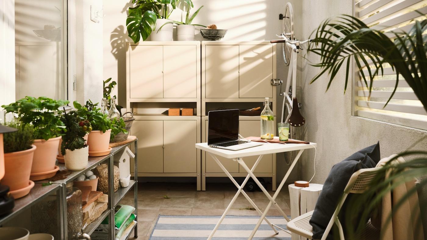 Une table de salle à manger d'extérieur blanche avec ordinateur portable, quatre armoires métalliques beiges empilées deux par deux, différentes plantes et un vélo blanc accroché au mur.