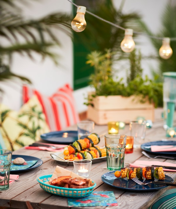 Une table d'extérieur en bois, entourée de plantes, de guirlandes lumineuses et de textiles, avec des assiettes FÄRGRIK et des couverts LIVNÄRA.