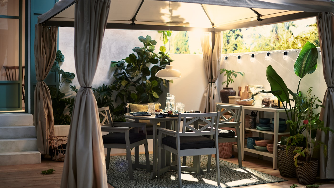 Une table d'extérieur et des chaises BONDHOLMEN grises organisées pour que quatre personnes puissent profiter d'un dîner en plein air sur la terrasse, sous une tonnelle en tissu.
