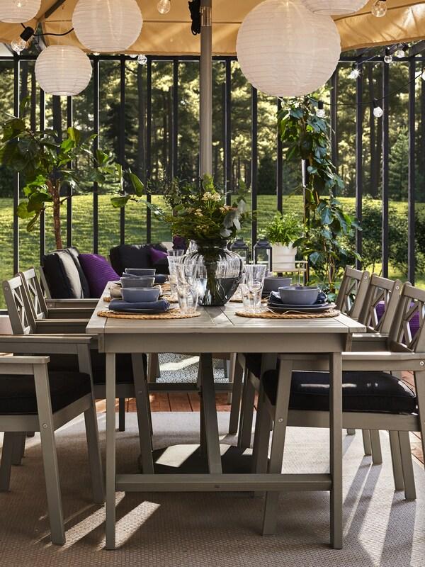Une table d'extérieur grise, six chaises grises à accoudoirs et coussins de siège noirs. Vaisselle bleue sur la table.