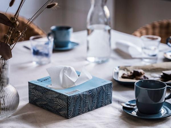 une table dressée avec de la vaisselle bleue et une boîte de mouchoir assortie est placée au centre