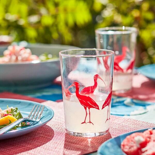 une table dressée avec des verres de flamants sur des sets de table roses et avec une vaisselle turquoise dans un jardin