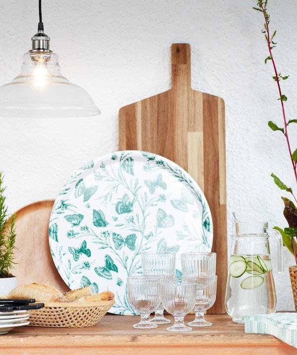 Une table dressée pour le déjeuner, avec des verres, du pain, des serviettes, des assiettes, un plateau vert et une planche à découper en bois.
