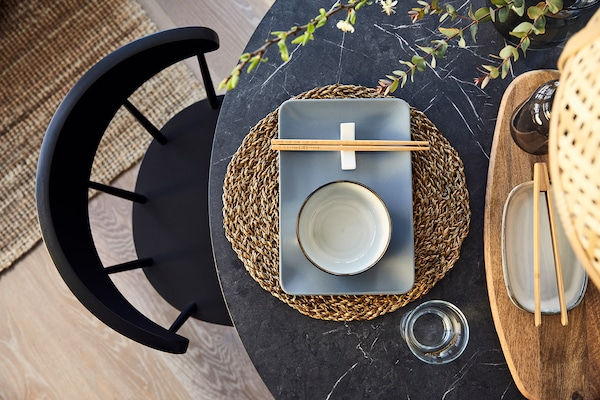 Une table effet marbre noire avec des assiettes gris foncées et un set de table en jacinthe d'eau.