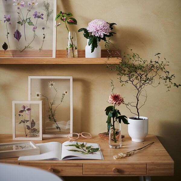 Une table en bois avec des fleurs dans des vases et d'autres fleurs séchées dans des cadres.