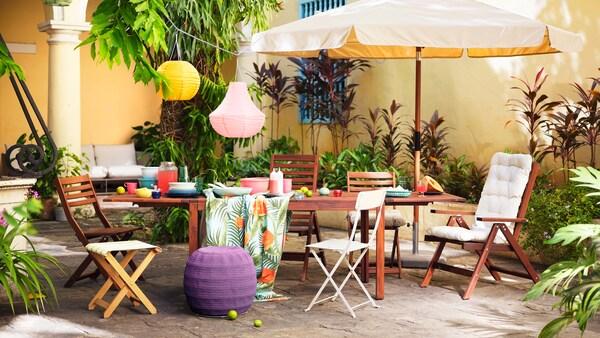 Une table en bois et diverses chaises disposées à l'extérieur contre un mur jaune, avec un parasol et des lanternes colorées.