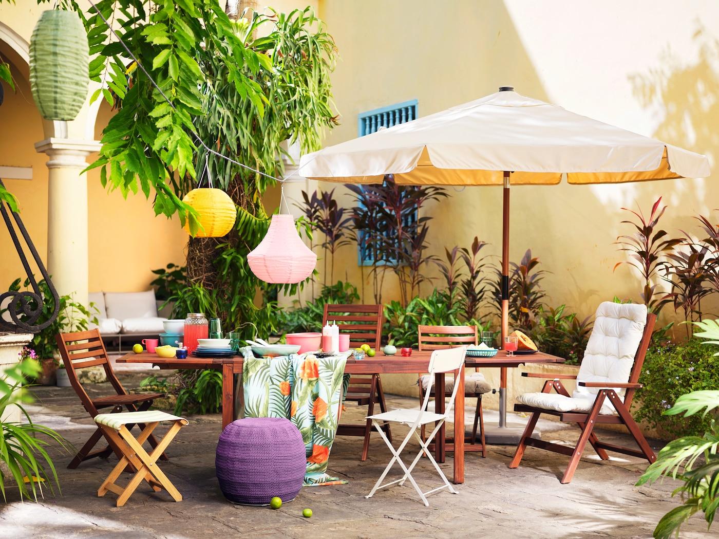 Une table en bois et une grande variété de chaises placées à l'extérieur contre un mur jaune, avec un parasol et des lanternes colorées.