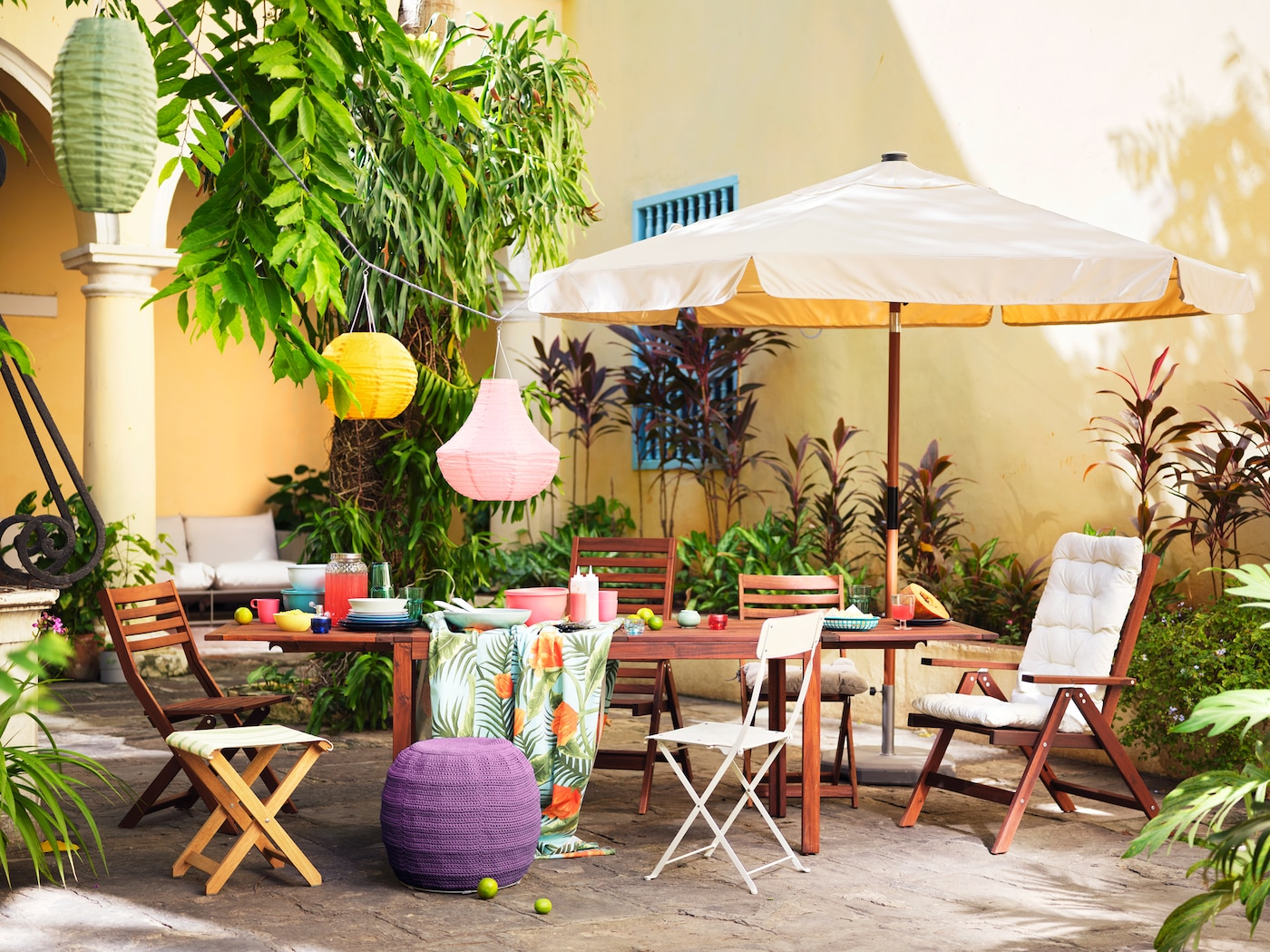 Une table en bois et une variété de chaises disposées à l'extérieur contre un mur jaune, avec un parasol et des lanternes colorées.