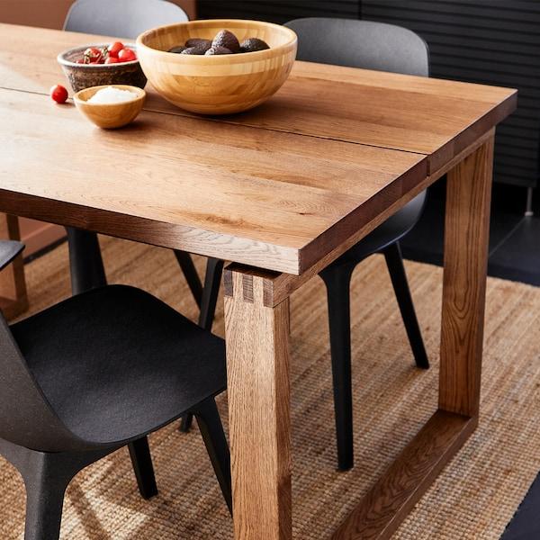 Une table en bois MÖRBYLÅNGA brun clair présentant les veinures et variations de couleur naturelles du chêne, assortie à des chaises modernes plus foncées.